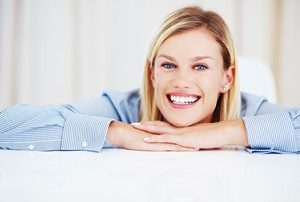 Closeup of cheerful young female executive smiling while looking at you